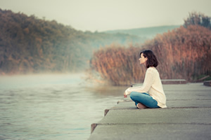 Lady meditating and doing Reiki by a lake